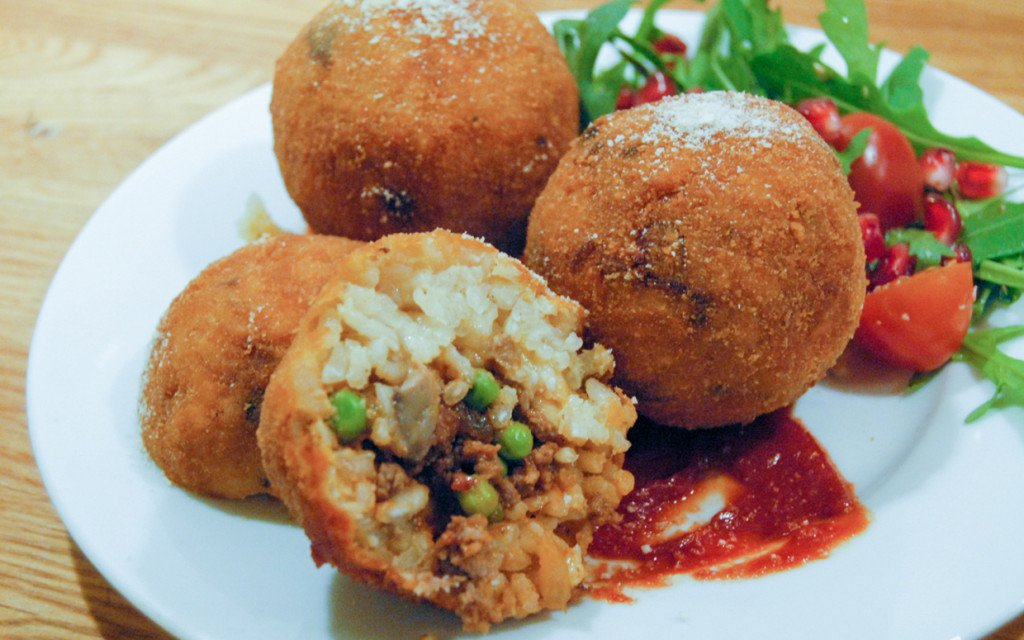Arancini are crispy stuffed rice balls and are a must try when in Italy. ouritalianjourney.com